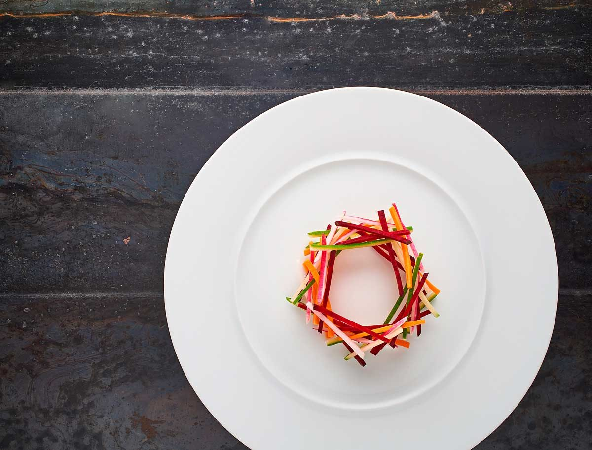 juliennes de légumes taillés dans une assiette plate en porcelaine blanche